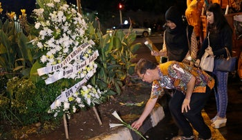 Indonesians lay flowers near the police post where an attack took place in Jakarta, Indonesia, January 14, 2016.