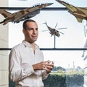Shmayim founder Ofir Paldi standing beneath models of two aircraft and a helicopter.