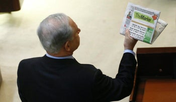 Prime Minister Benjamin Netanyahu reads a copy of TheMarker, Haaretz's economic sister publication, in the Knesset. 2010.