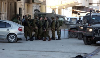 Israeli security forces gather at the site of a reported stabbing attack at the Huwara checkpoint near the West Bank city of Nablus, on December 27, 2015.