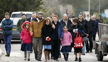 The husband and children of Dafna Meir, 39, walk together upon their arrival to her funeral ceremony in the West Bank Jewish settlement of Otniel January 18, 2016.