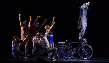 """Pilobolus in """"The Inconsistent Pedaler."""" A bicycle is at center stage, with a man in what appears to be a clown suit standing on its handlebars. Behind him are five people, their upraised arms holding fist-sized rubber duckie bath toys."""