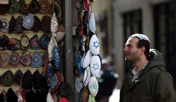 A Jewish man looks at skullcaps on display at a Kippa store in downtown west Jerusalem, on January 15, 2016.