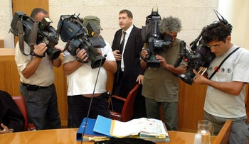 Illustrative photo: Israeli human rights lawyer stands in court (center) while reporters film documents on a desk.