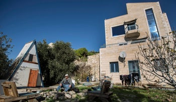 In this photo taken Sunday, Jan. 17, 2016, Moshe Gordon sits outside his guest house advertised on Airbnb international home-sharing site in Nofei Prat settlement at the West Bank.
