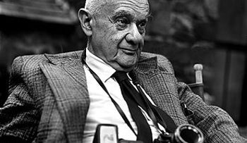 Roman Vishniac, seated, wearing suit and tie and his trademark camera, 1977.