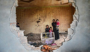 A women and her children stand in the ruins of battle-damaged house in the Kurdish town of Silopi, southeastern Turkey, January 19, 2016.