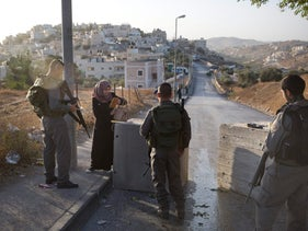 Israeli border police check a Palestinian woman's ID next to newly placed concrete blocks in an East Jerusalem neighborhood, Oct. 15, 2015.