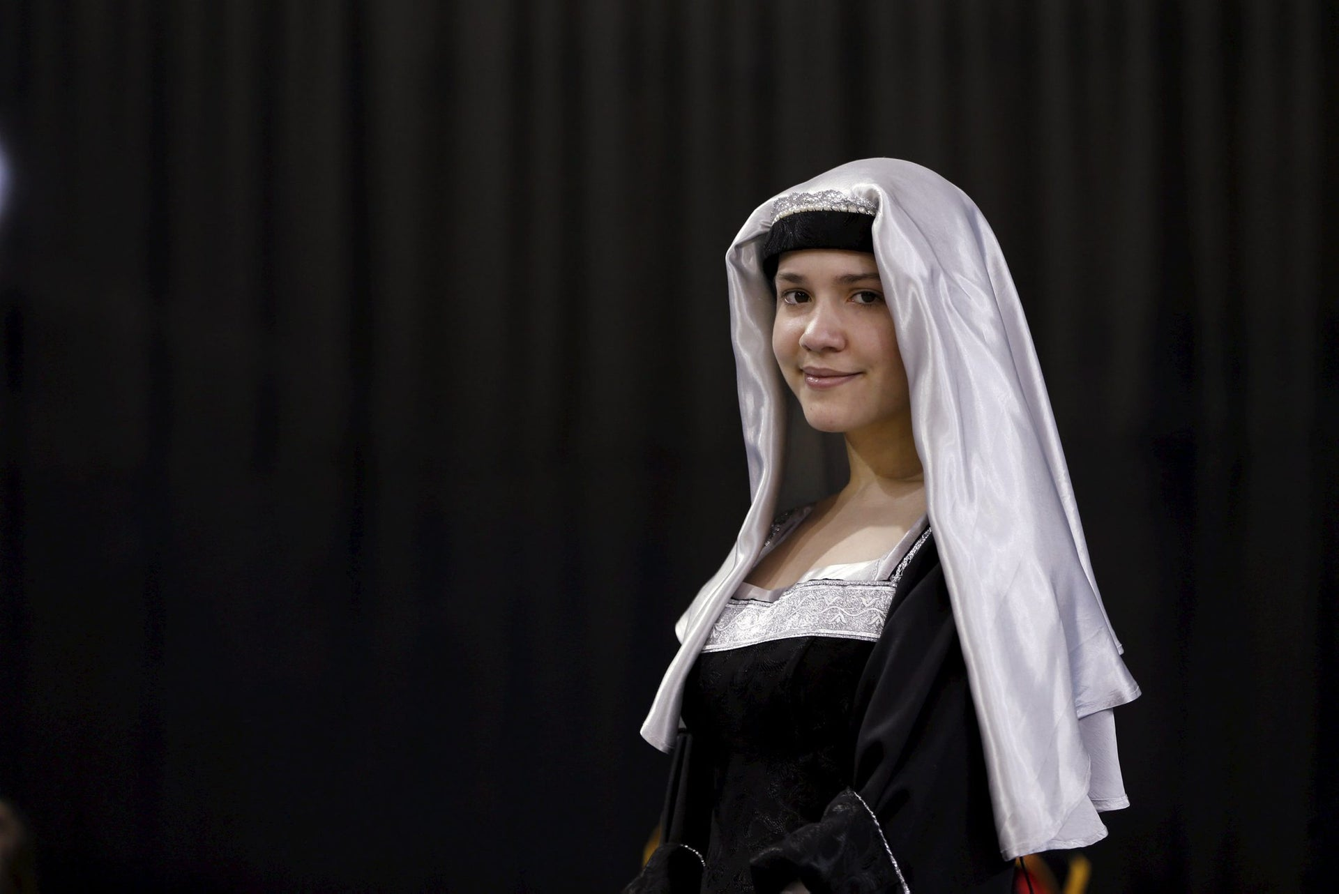 A woman stands in a medieval costume during an international medieval tournament in Tel Aviv, January 23, 2016.