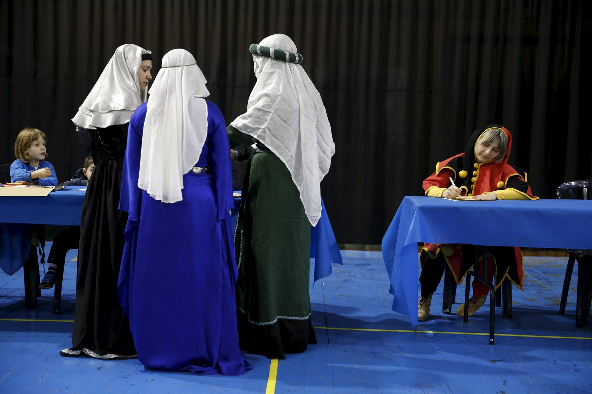 Women in historical dresses stand together during an international medieval tournament in Tel Aviv, January 23, 2016.