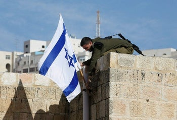 A soldier removes Israeli flag from a house as troops forcibly evict Jewish settlers from homes they illegally entered in Hebron, January 22, 2016.