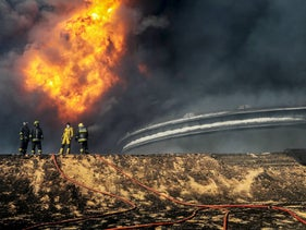 Firefighters try to put out the fire in an oil tank in the port of Es Sider, in Ras Lanuf, Libya, January 6, 2016.
