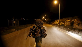 An Israeli soldier guards near the Jewish settlement of Otniel in the West Bank January 17, 2016, after a female resident of the settlement was stabbed to death.