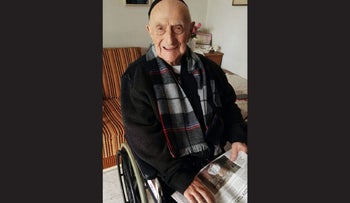 Yisrael Kristal of Haifa reads the Haaretz article on him possibly being the oldest living man.