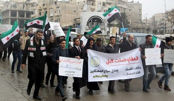"Residents carry banners reading ""No negotiations before: the cessation of the shelling, the lifting of the siege and the release of the prisoners"" as they march, Aleppo, Syria, January 24, 2016."