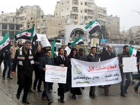 """Residents carry banners reading """"No negotiations before: the cessation of the shelling, the lifting of the siege and the release of the prisoners"""" as they march, Aleppo, Syria, January 24, 2016."""