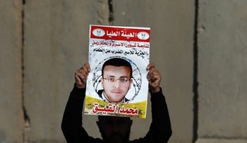 A Palestinian man carrying a placard bearing a portrait of Palestinian journalist Mohammed al-Qiq at a demonstration north of Ramallah.