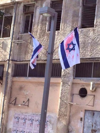 Israeli flags splashed with red paint in Jaffa.