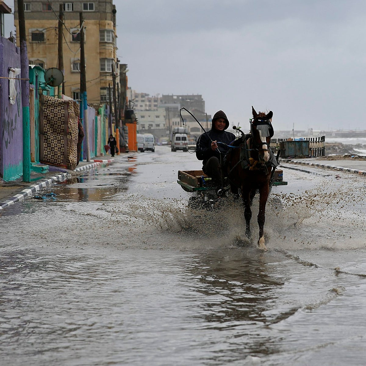 A Palestinian man drives his horse-drawn cart through a flooded beach-side street, in Gaza City, Tuesday, January 26, 2016.