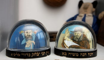"Kabbala snow globes: On the left, one extolling ""Maran Yitzhak Kedouri, may he live long"" and the other featuring the Lubavitcher Rebbe, Menachem Mendel Schneersohn, with the caption ""The Messiah is coming""."