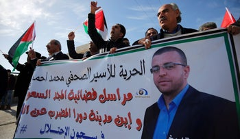 Palestinian demonstrators near Ramallah demand release of hunger-striking Palestinian journalist Mohammed Al-Qiq (portrait) from Israeli jail, January 22, 2016.
