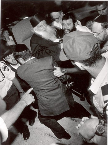 Rabbi Yitzhak Kedouri being carried by supporters, election season, 1996. Coined a kingmaker for his influence over potential voters, some worried that the rabbi was being led, rather than leading.