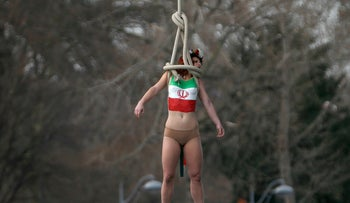 A topless activist of women's rights group FEMEN hangs from a bridge as they stage a protest against Iran's President Hassan Rouhani visit to Paris, France, January 28, 2016.