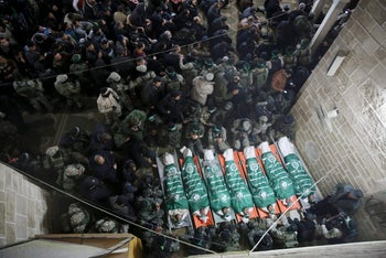 Palestinian militants pray by the bodies of seven Hamas member killed repairing a tunnel during their funeral at a mosque in Gaza City, Friday, Jan. 29,
