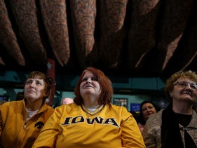 "Supporters of democratic presidential candidate former Secretary of State Hillary Clinton look on during a ""get out the caucus"" event at The Col Ballroom on January 29, 2016 in Davenport, Iowa."