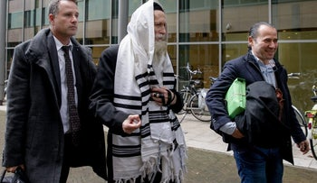 Rabbi Eliezer Berland, center, outside a Dutch court on November 17, 2014.