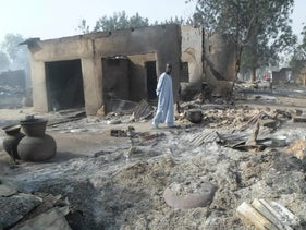 A man walks past burnt out houses following an attack by Boko Haram in Dalori village, Nigeria, January 31, 2016.