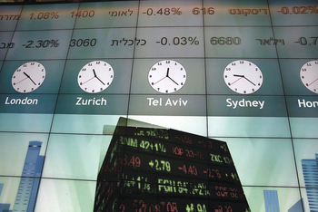 Stock prices flash on an electronic screen displaying world clocks at the Tel Aviv Stock Exchange (TASE) in Tel Aviv, Israel, on Thursday, Dec. 11, 2014.
