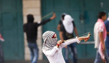A Palestinian woman uses a slingshot during clashes with Israeli troops in the West Bank city of Bethlehem on Tuesday, Oct. 13, 2015.