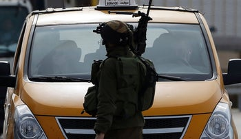 Israeli soldier checks the vehicles of Palestinians on their way out of the West Bank village of Ein Sinya, northern Ramallah on February 1, 2016.