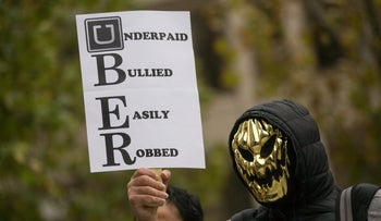 An Uber driver wearing a mask holds up a sign during a protest against a rise in the commission taken by Uber Technologies Inc. outside its offices in London, in November 2015.