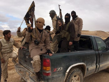 Al-Qaida-linked Nusra Front fighters carry their weapons on the back of a pick-up truck during the release of Lebanese soldiers and policemen in Arsal, eastern Bekaa Valley, Lebanon, December 1, 2015.