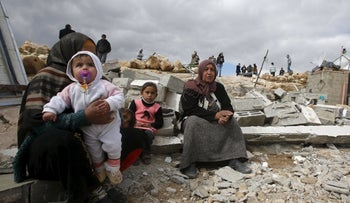Palestinians sit among the rubble of their house, which was demolished by Israeli bulldozers, in the West Bank village of Jimba, southern Hebron February 2, 2016.