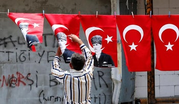 A man displays Turkey's national flags and flags printed with portraits of Mustafa Kemal Ataturk, the founder of secular Turkey.