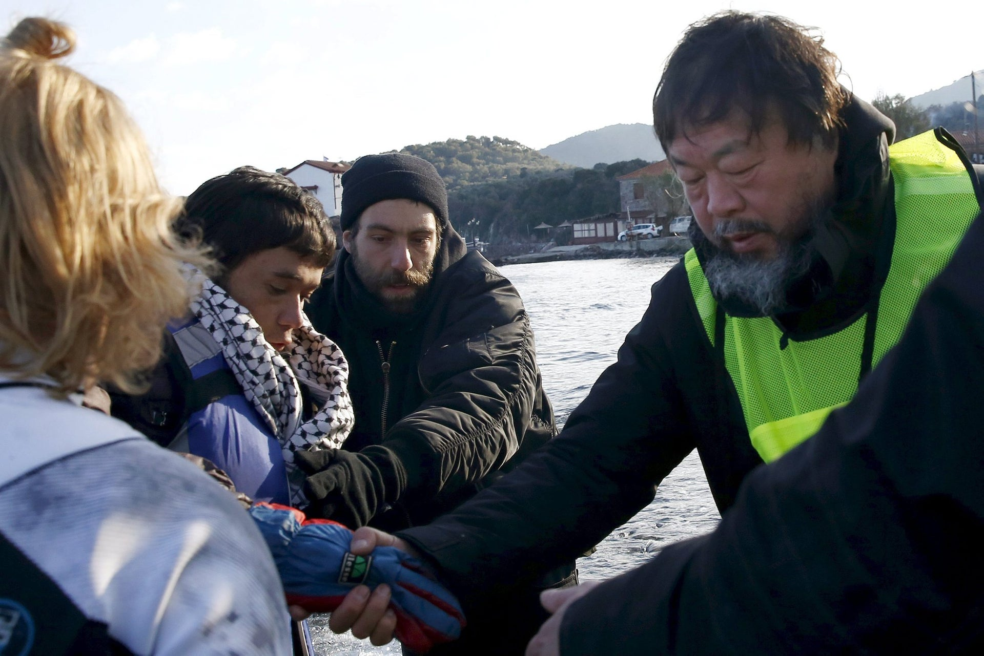 Chinese artist Ai Weiwei (R) helps an Afghan migrant as he arrives with other refugees and migrants on a raft on the Greek island of Lesbos, January 25, 2016.