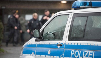 A police car stands outside a refugee shelter on February 4, 2016 in Attendorn after a raid during which a suspect was arrested.