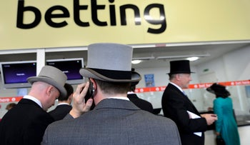 Racegoers queue to place bets during the first day of the Royal Ascot horse-racing festival in England, June 2013