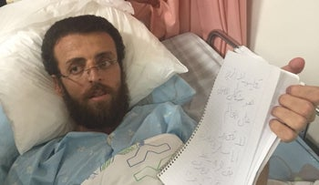Mohammed Al-Qiq communicates from his hospital bed.
