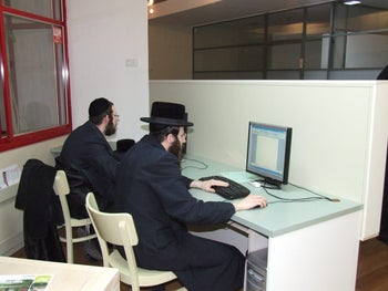 Two ultra-Orthodox workers in front of computers in an office in 2014.