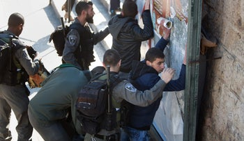 Israeli border police body-search Palestinian men following an attack by three Palestinian assailants at Damascus Gate, a main entrance to Jerusalem's Old City on February 3, 2016.