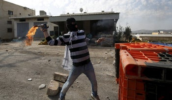 A Palestinian protester hurls a molotov cocktail towards Israeli troops during clashes in the West Bank town of Qabatiyah, near Jenin February 5, 2016.