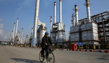 An Iranian oil worker rides his bicycle at the Tehran's oil refinery south of the capital Tehran, Iran, Dec. 22, 2014.