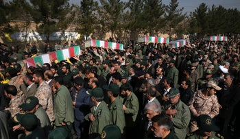 Civilians and armed forces members carry the flag draped coffins of Iranian Revolutionary Guard's Gen. Mohsen Ghajarian, and some of his comrades who were killed in fighting in Syria, Iran, today.