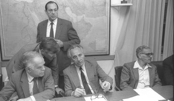 Then-Prime Minister Shimon Peres (center) during negotiations in 1985. Deputy prime minister Yitzhak Shamir is seated on the left.