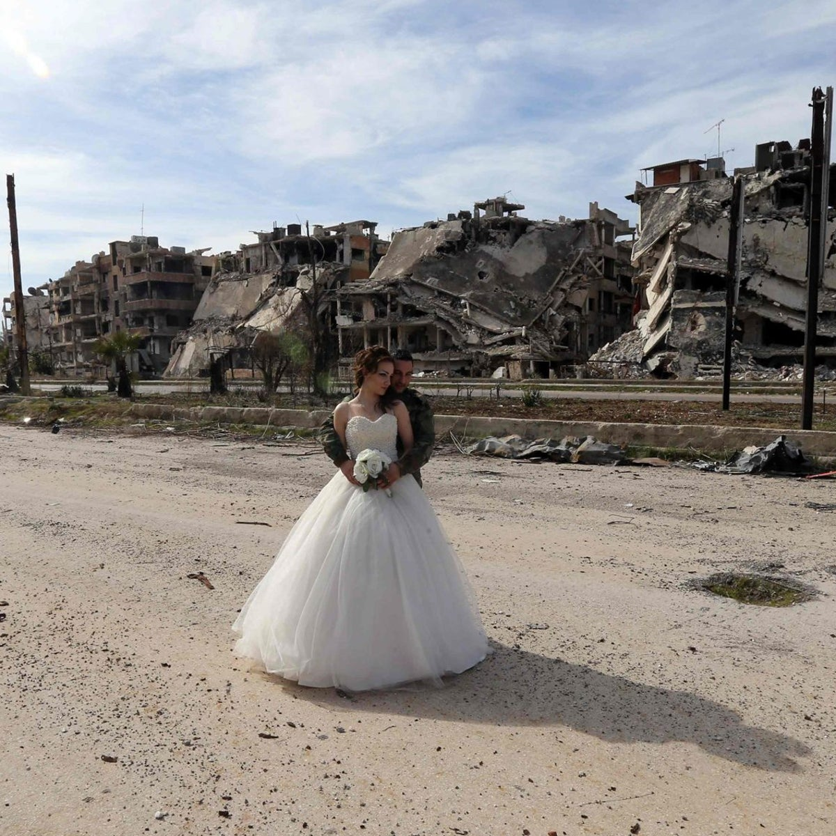 Nada Merhi and Hassan Youssef pose for wedding photos against the background of Homs, Syria, on February 5, 2016.