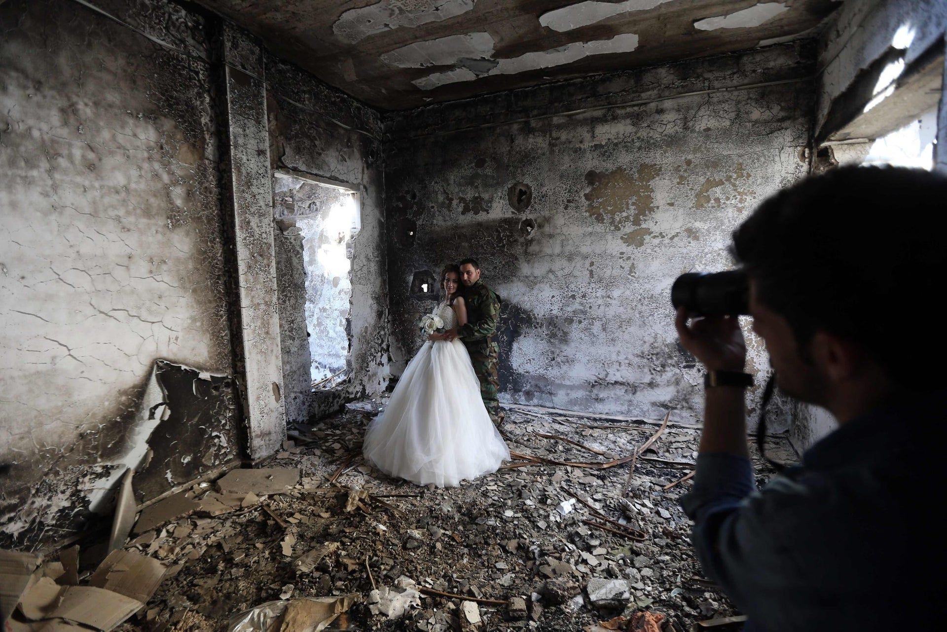 Newly-wed Syrian couple Nada Merhi,18, and Hassan Youssef,27, have their wedding pictures taken in a heavily damaged building in the war ravaged city of Homs on February 5, 2016.